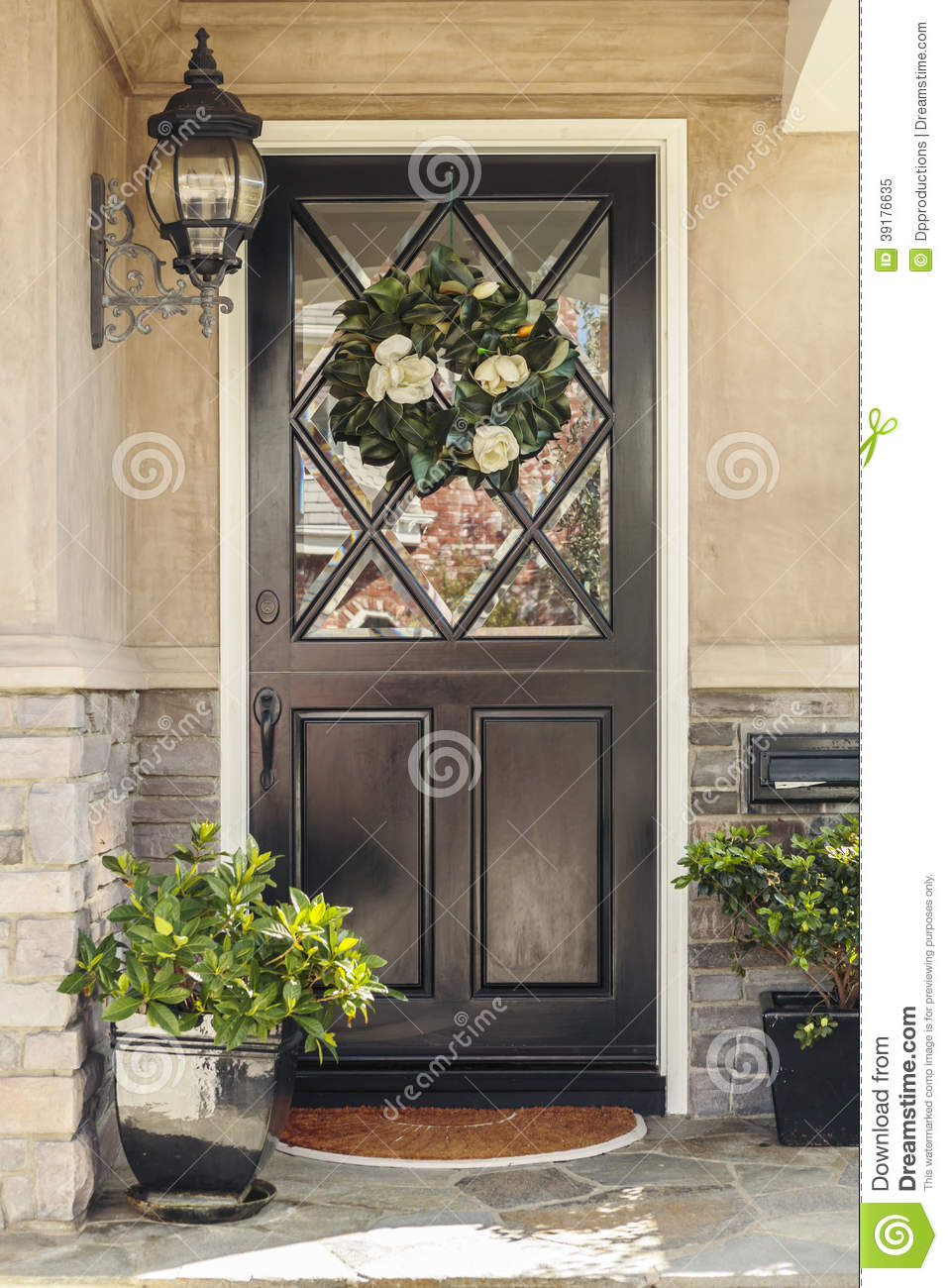 Black Front Door To Home With Flower Wreath Stock Photo