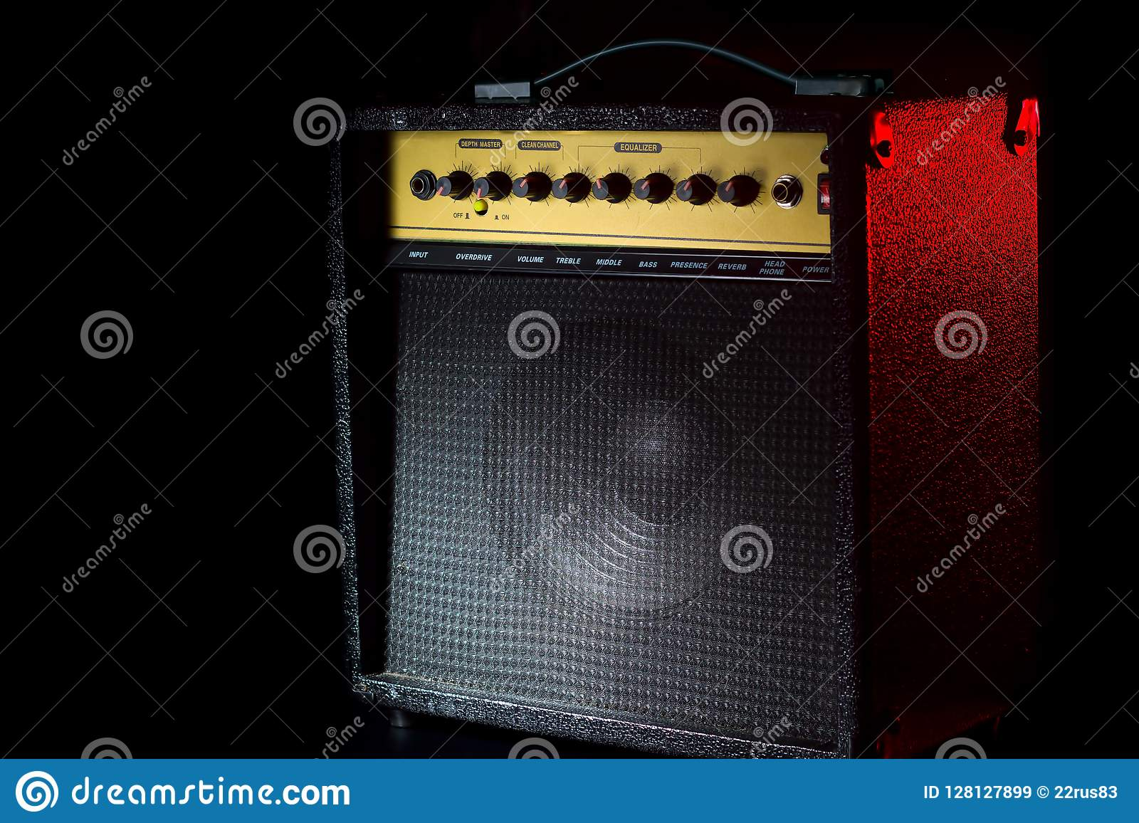 Black guitar amplifier on a black background with a red flash.