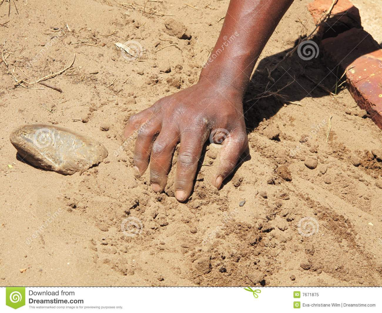 Black hand on sandy soil