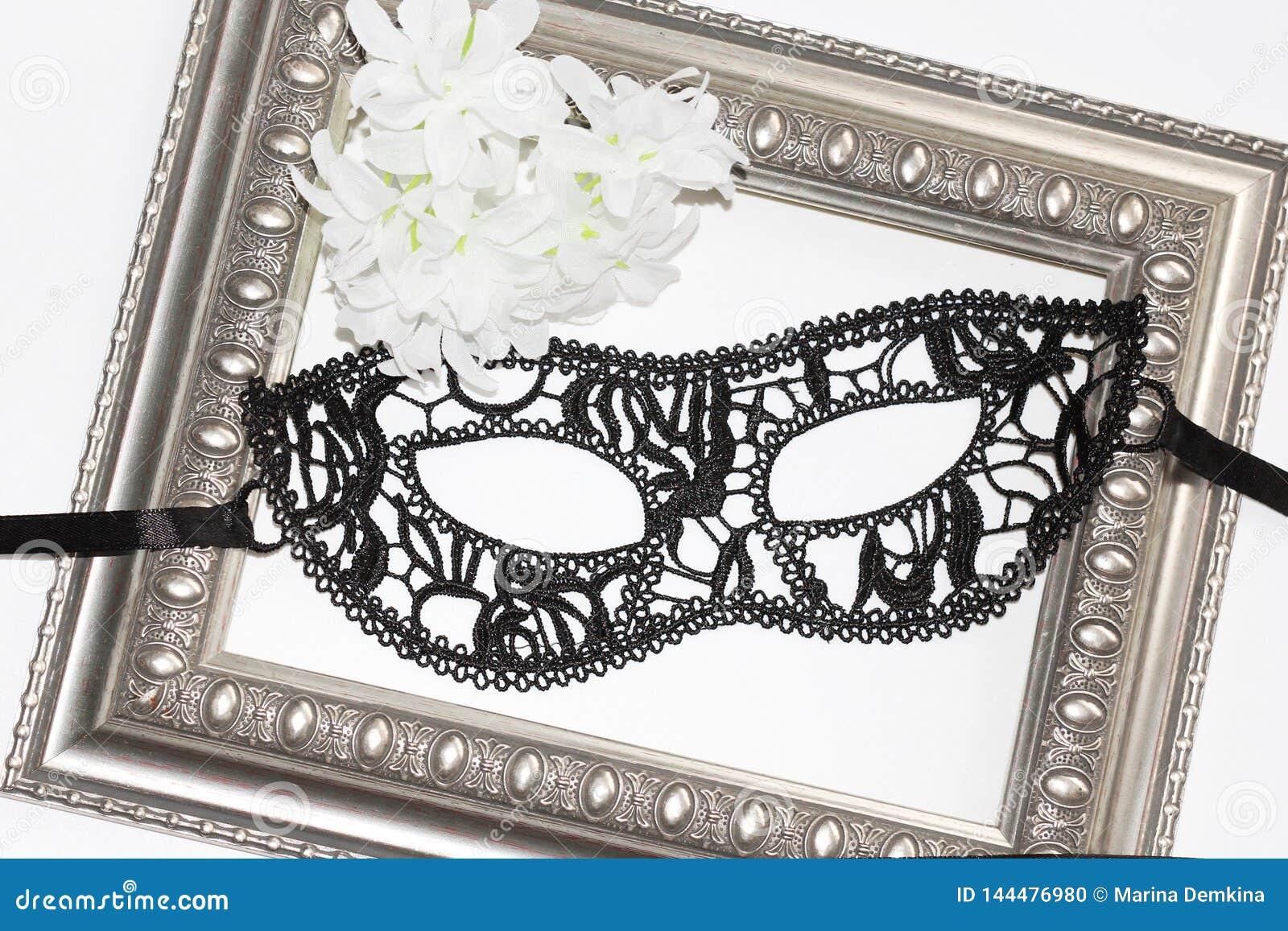 Black lace eye mask, vintage frame and white flowers