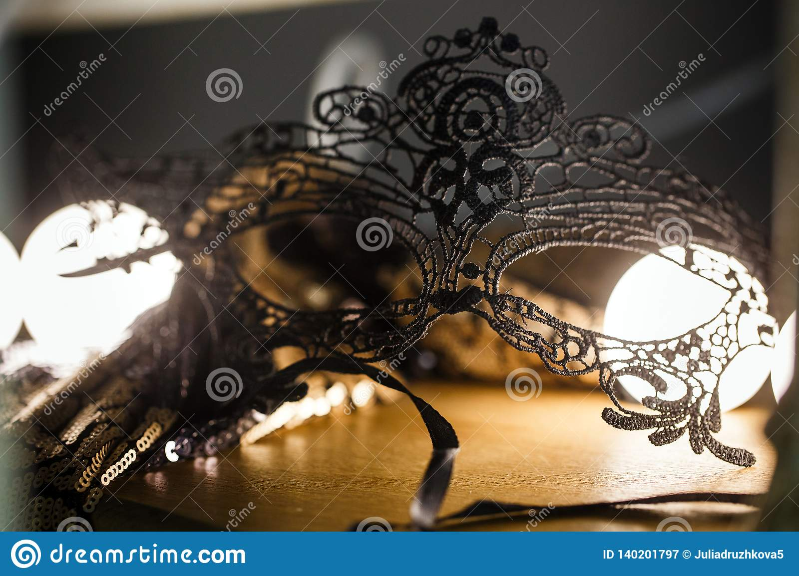 Black lace mask is on the table in a romantic atmosphere. Backlight, close-up