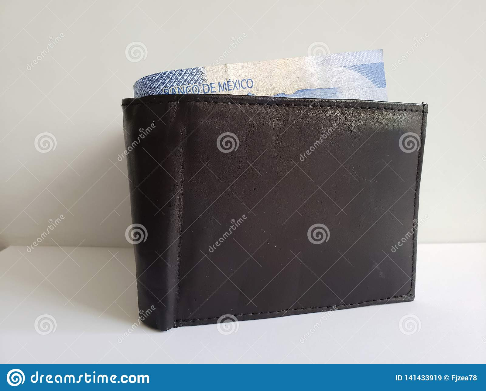black leather wallet with mexican banknotes and white background