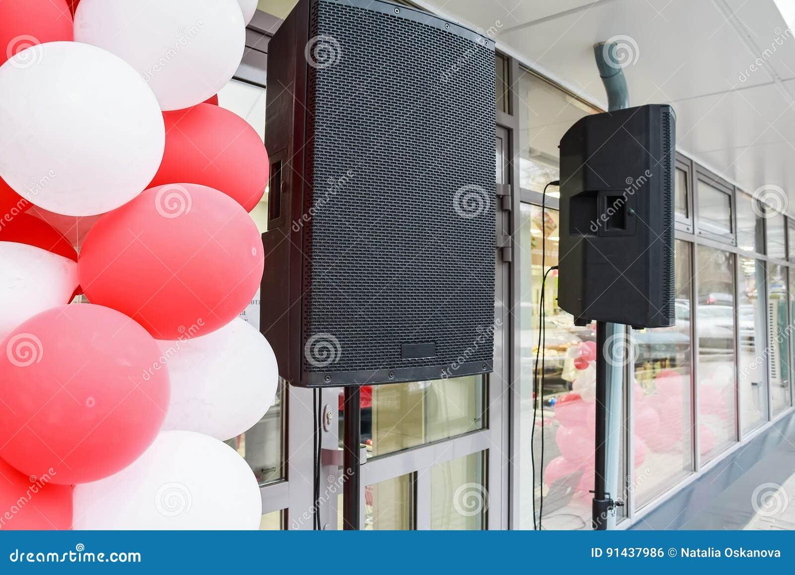 Black loudspeakers hang outside a shop