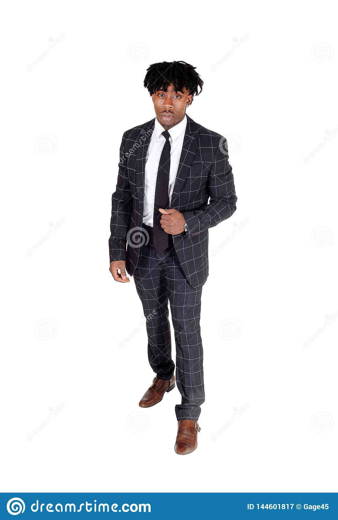 Black man in a dark suit standing in the studio with fussy black hair