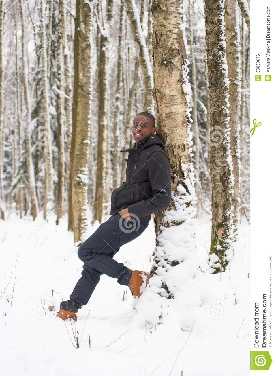 Black Man In The Snow Against A Tree Stock Photo