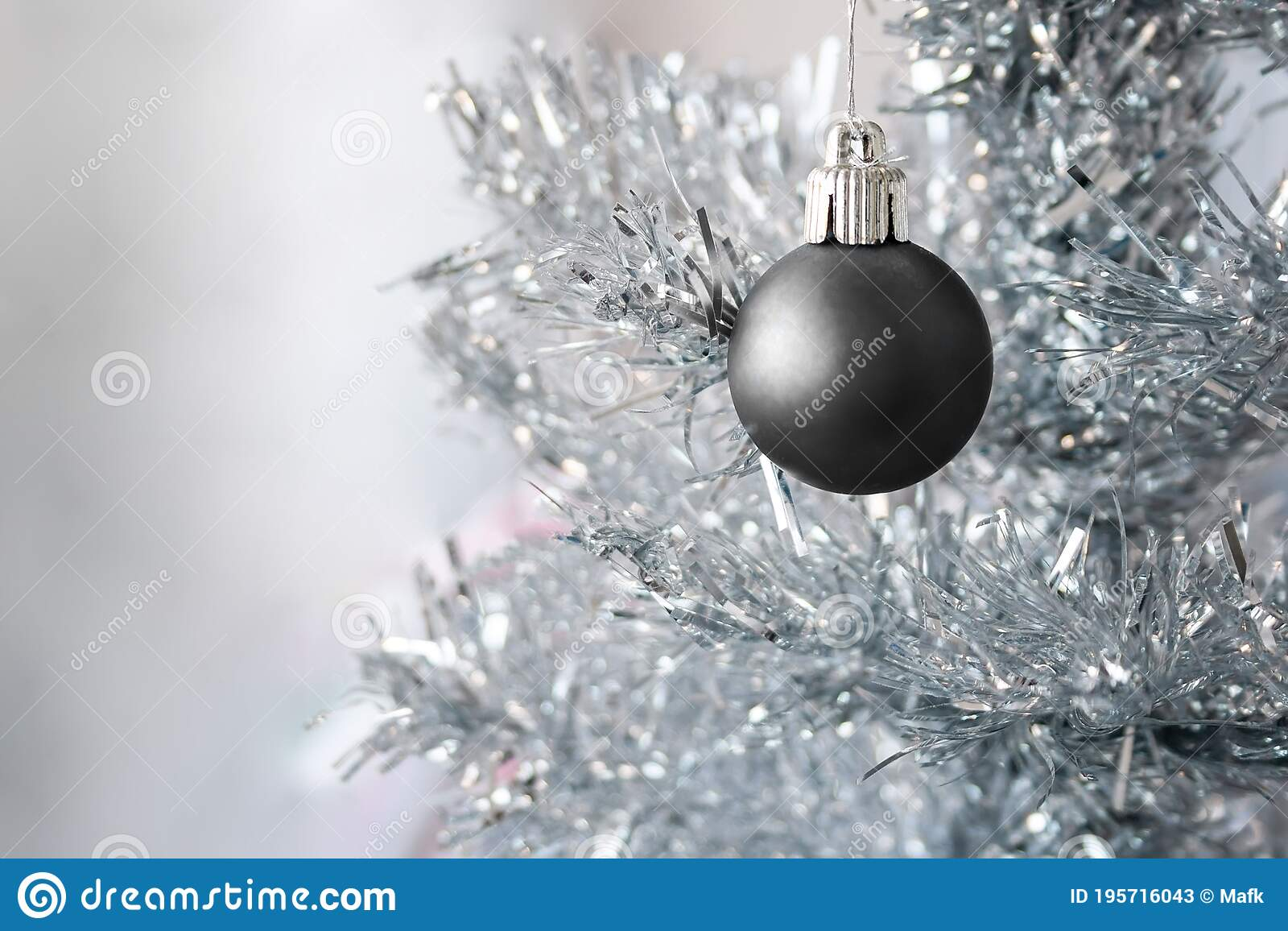Black Matte Metallic Ball Hanging On A Silver Artificial Christmas Tree With Copy Space Selective Focus Blurred Background Stock Image Image Of Matte Decoration 195716043