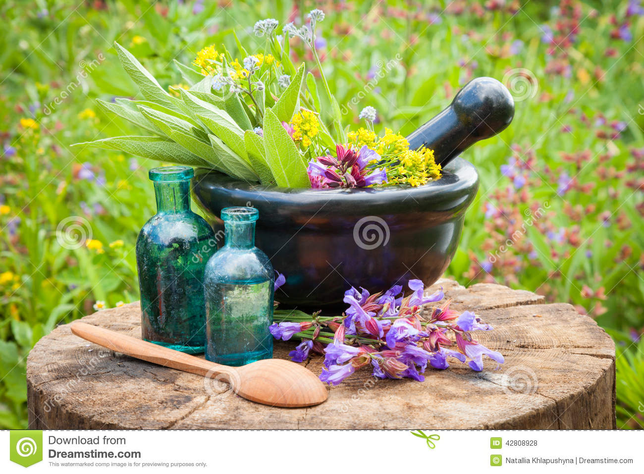 Black mortar with healing herbs and sage, glass bottle of oil