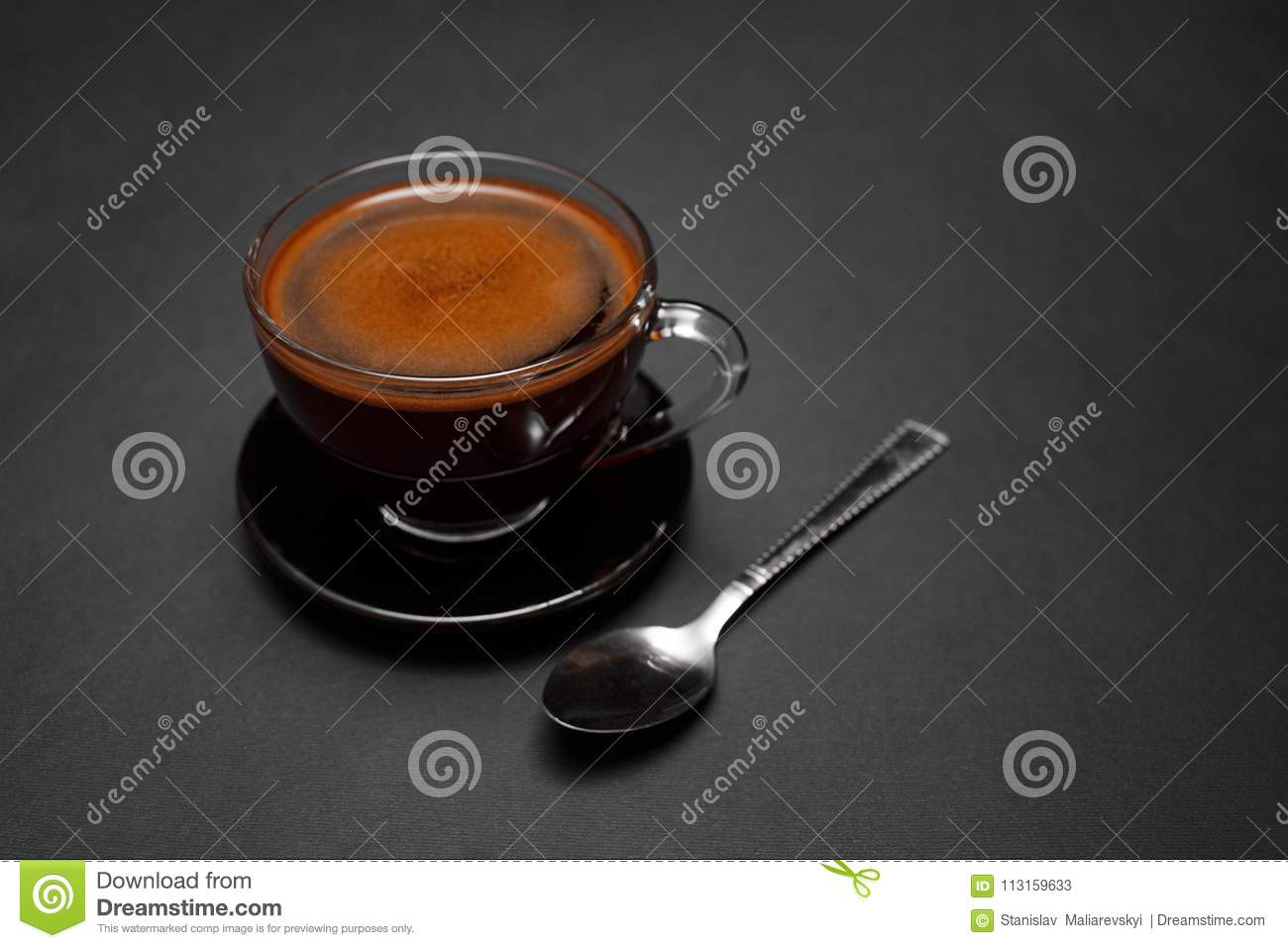 Black, natural, fragrant coffee in the transparent cup on a black background.