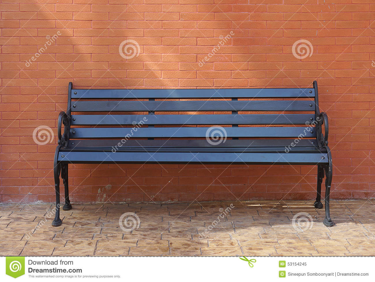 Black painted timber bench with brick wall background
