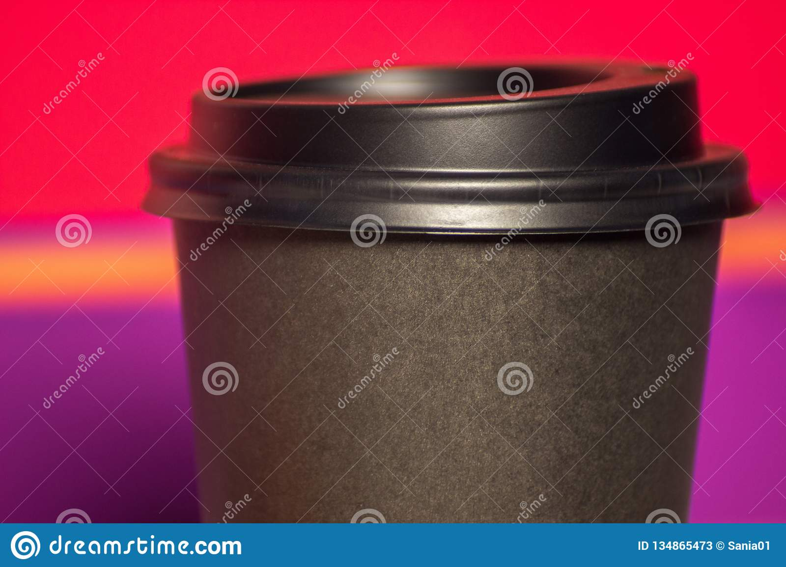 Black paper Cup with plastic lid. coffee or takeaway on a violet and pink background. brutal glass