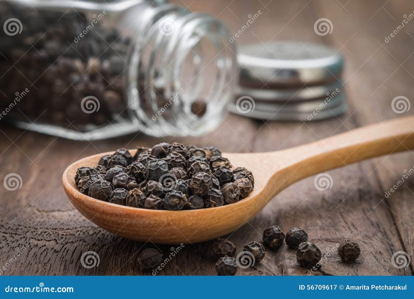 Black pepper on wooden spoon