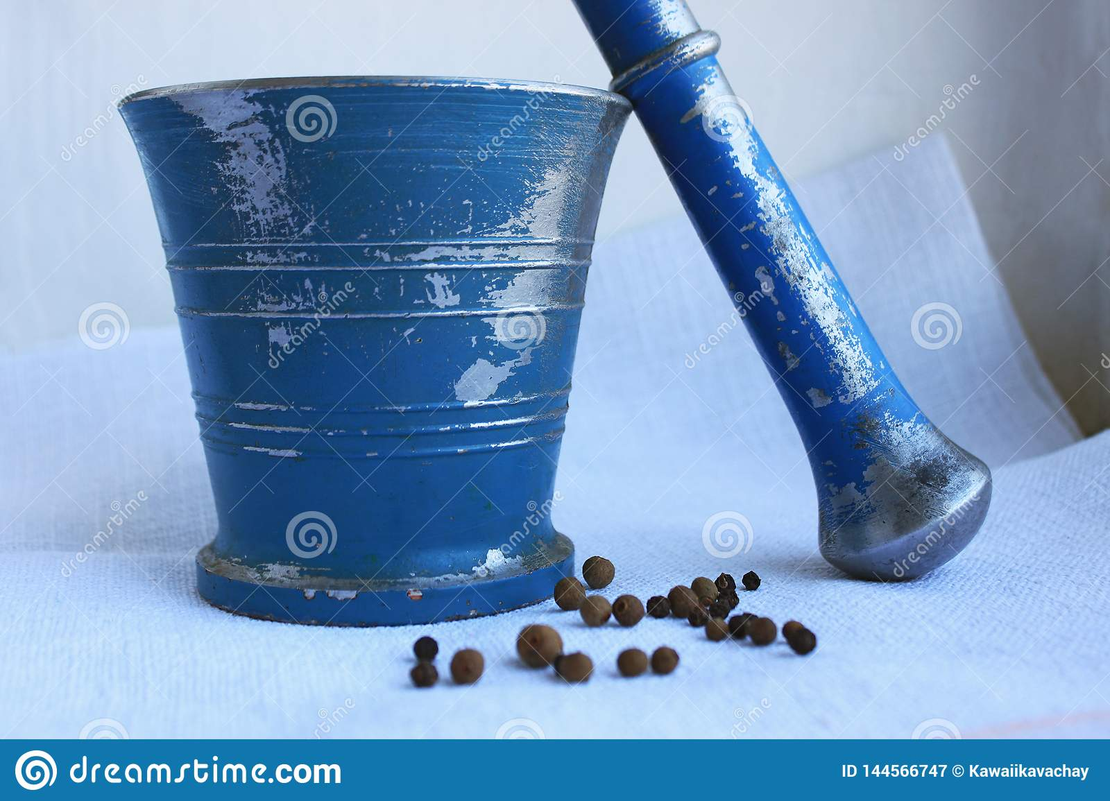 Black peppercorns and allspice in ancient metal mortar with pestle on linen background