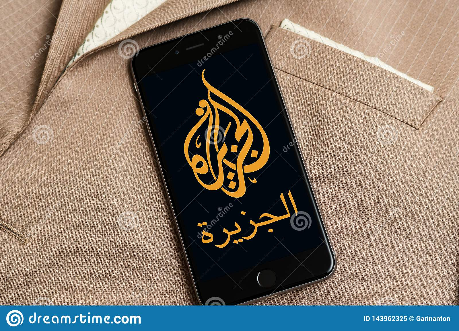Black phone with logo of news media Al Jazeera on the screen.