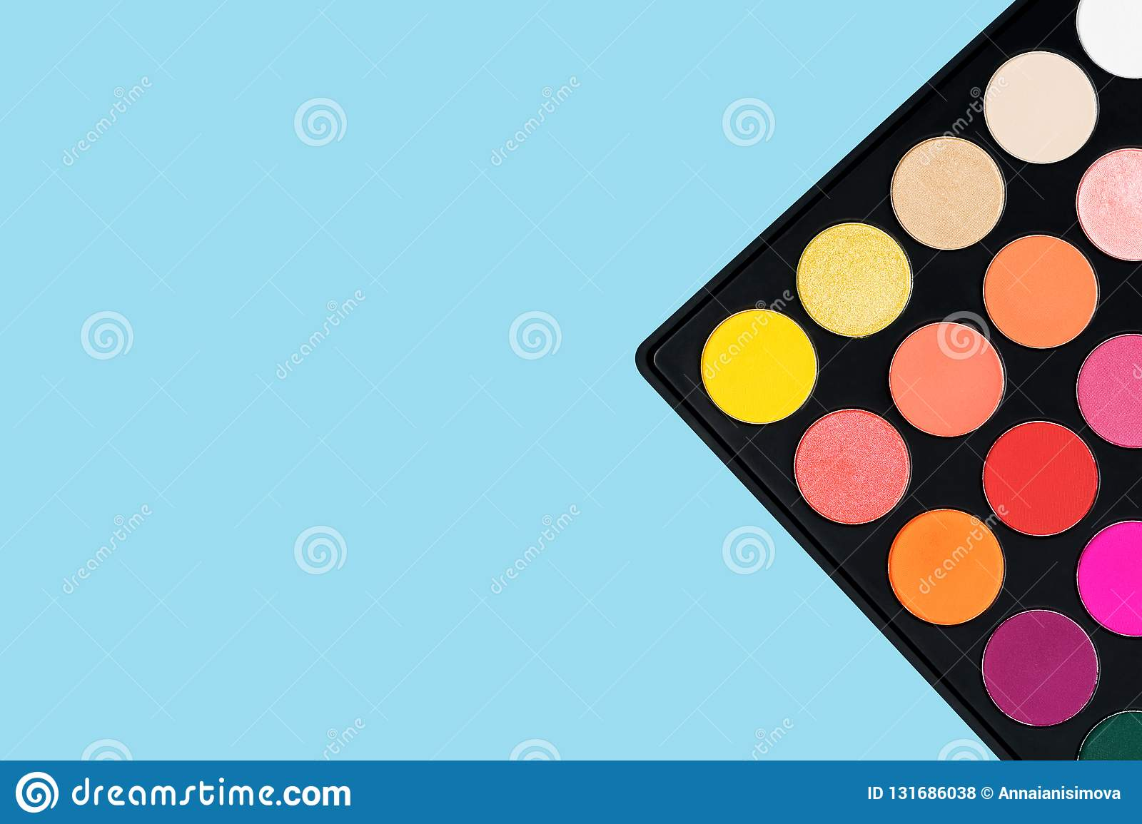 Black plastic palette of brightly coloured yellow, red, pink, orange eyeshadow placed in the corner of pastel baby blue background