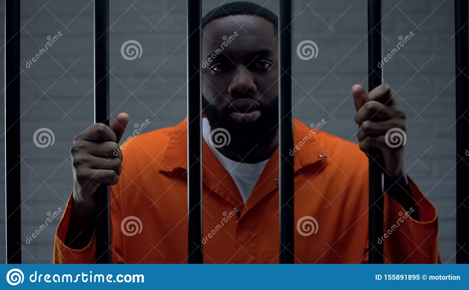 Black prisoner holding bars and looking at camera, drug dealer punishment