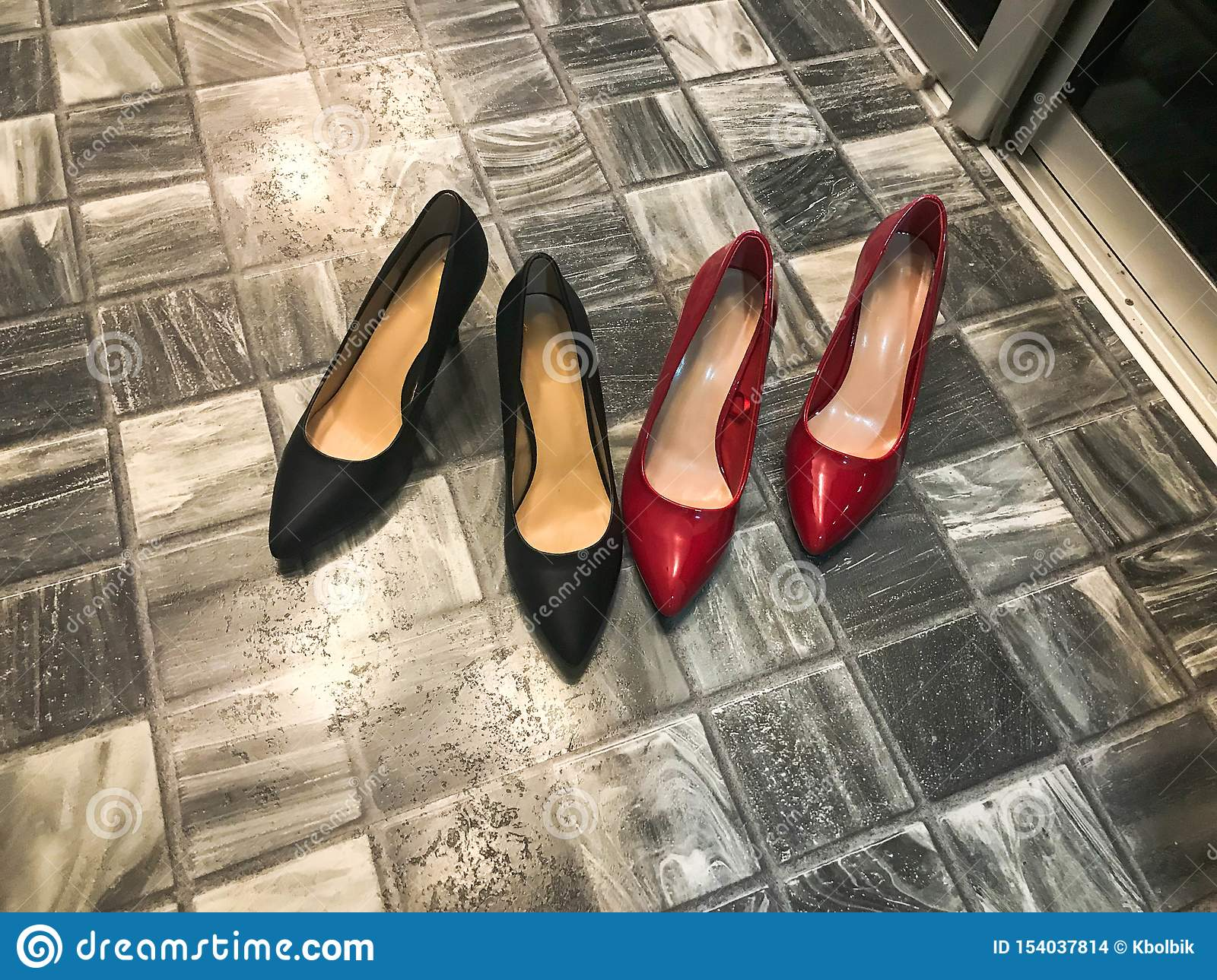 Black and red women`s beautiful elegant classic fashionable glamorous leather high-heeled shoes, stiletto heels against a stone