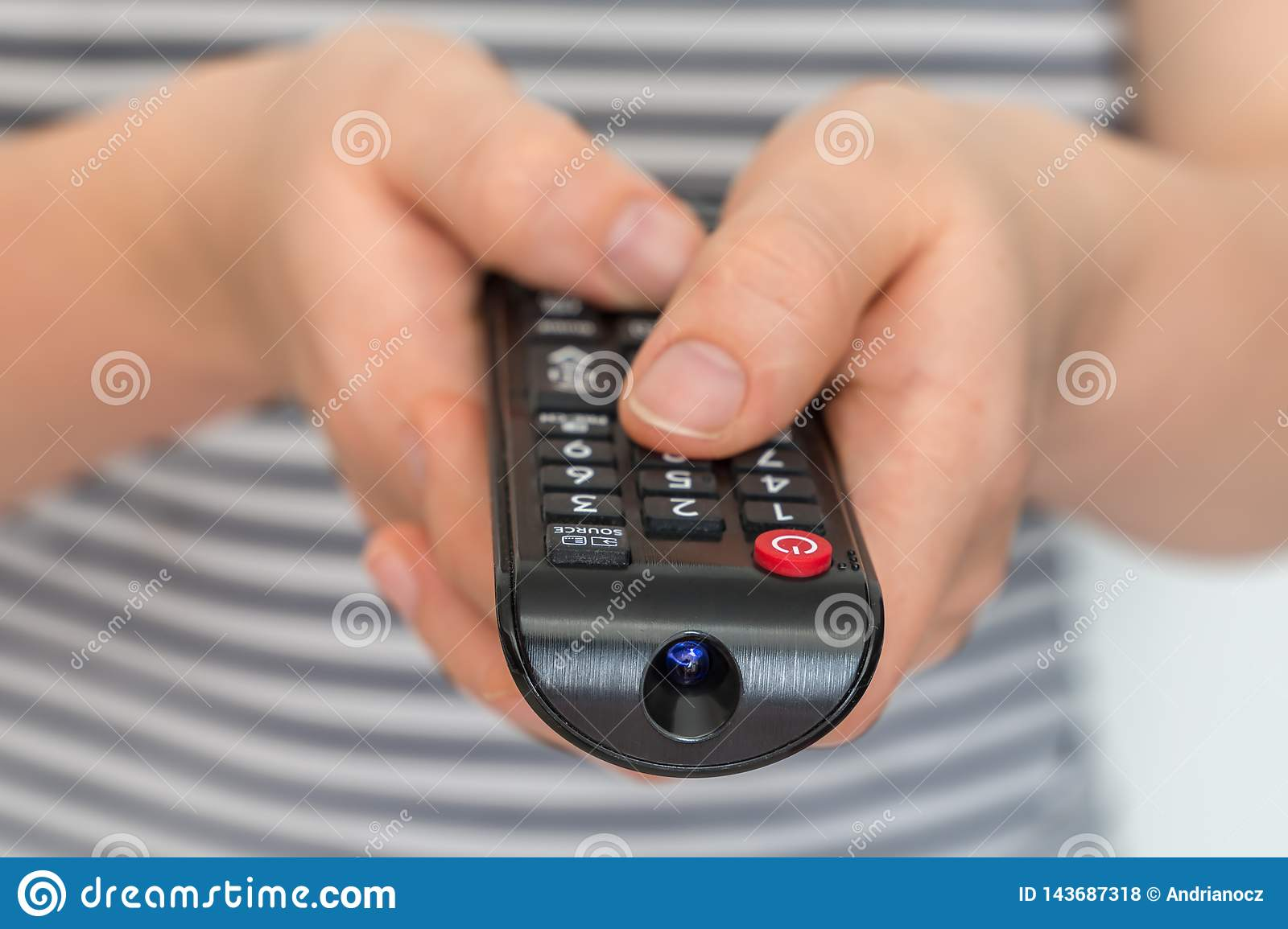 Remote control in female hands pointing to TV