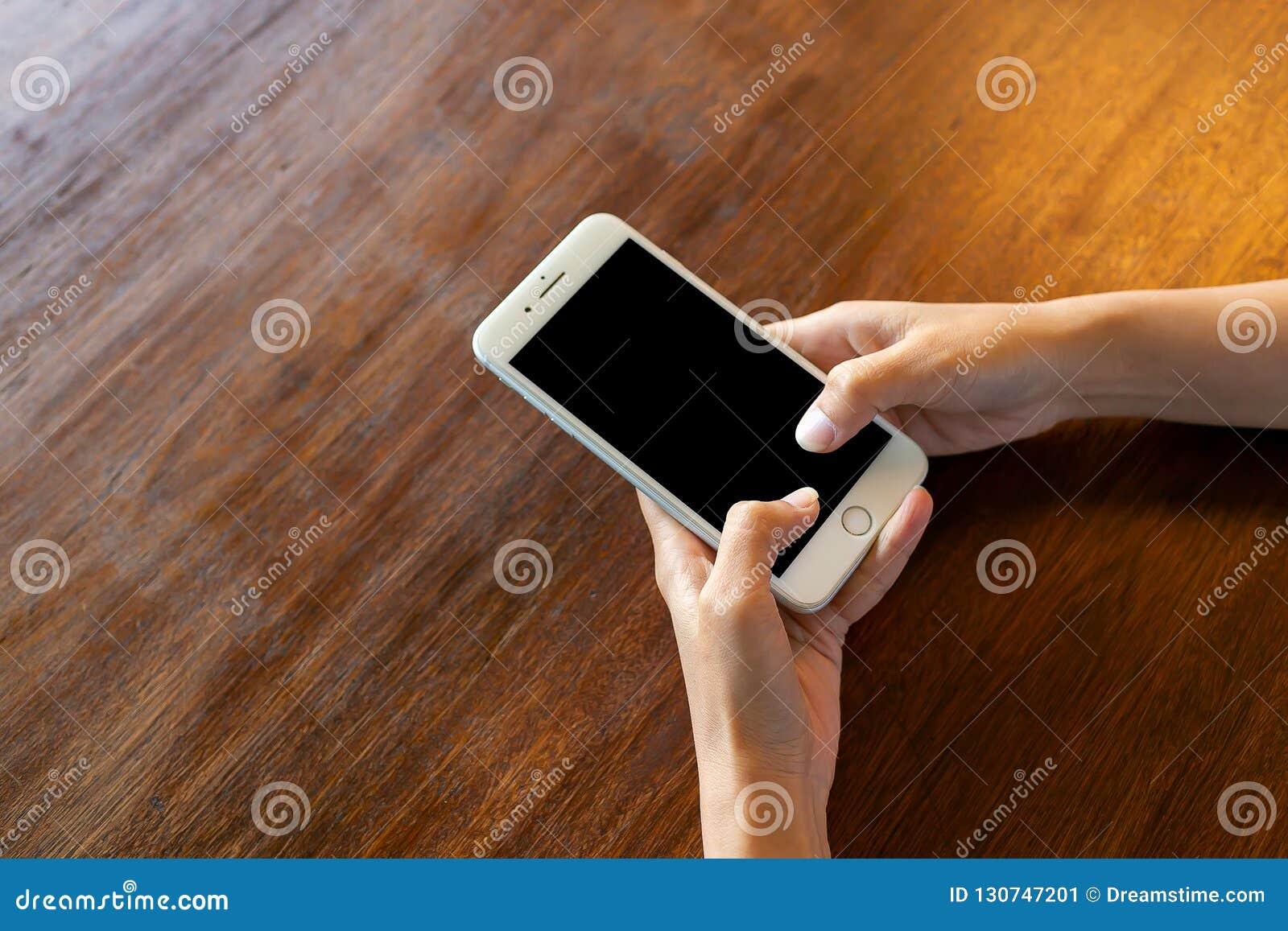 Black screen phone on wooden desk