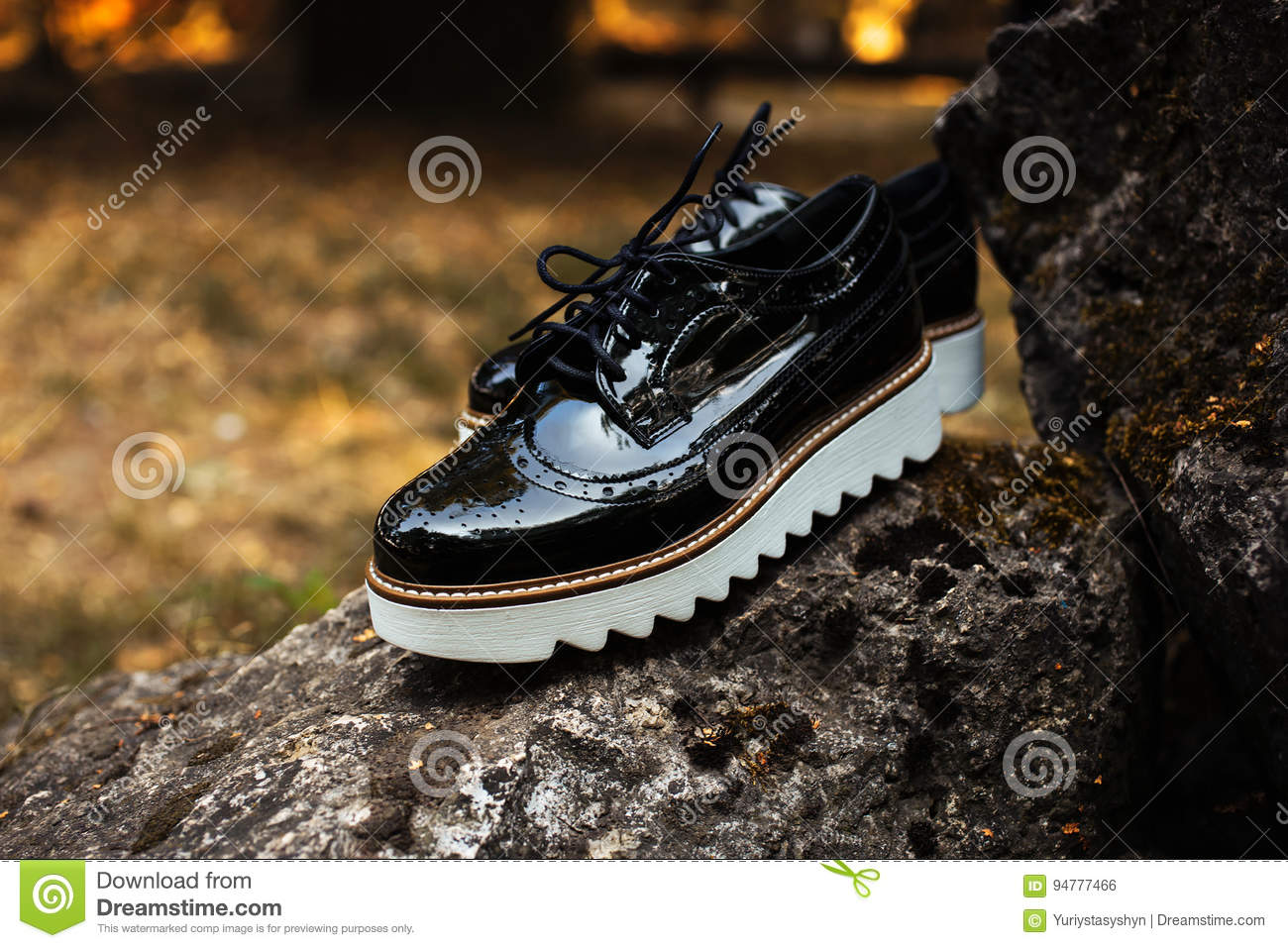 8b39d9da44d Black shiny patent leather women`s brogues shoes with white soles on old  gray stones