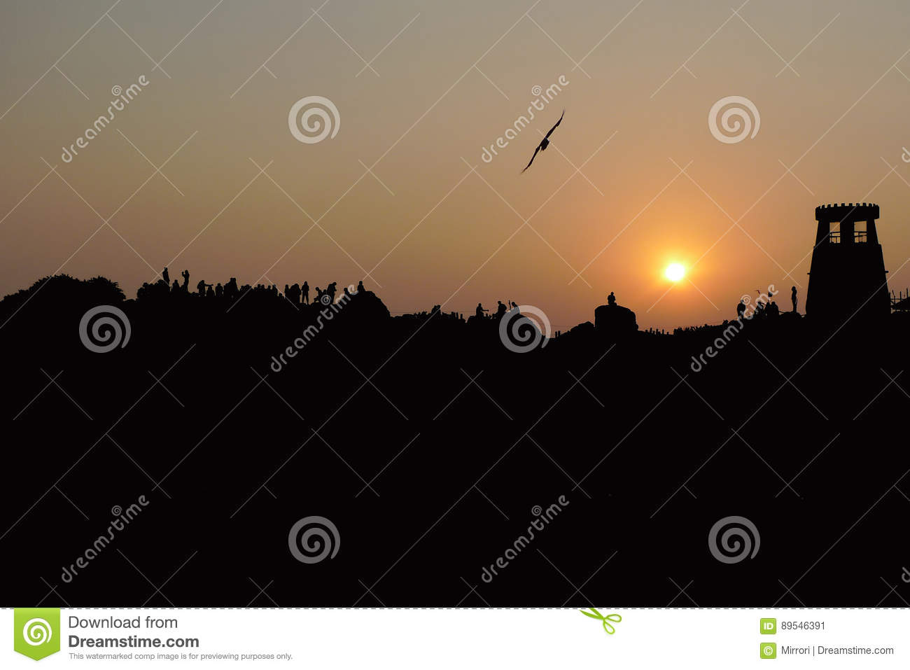 Black silhouette of the hill, people`s figures, a tower on the background of the orange sunset sky with a disc of the sun, in the