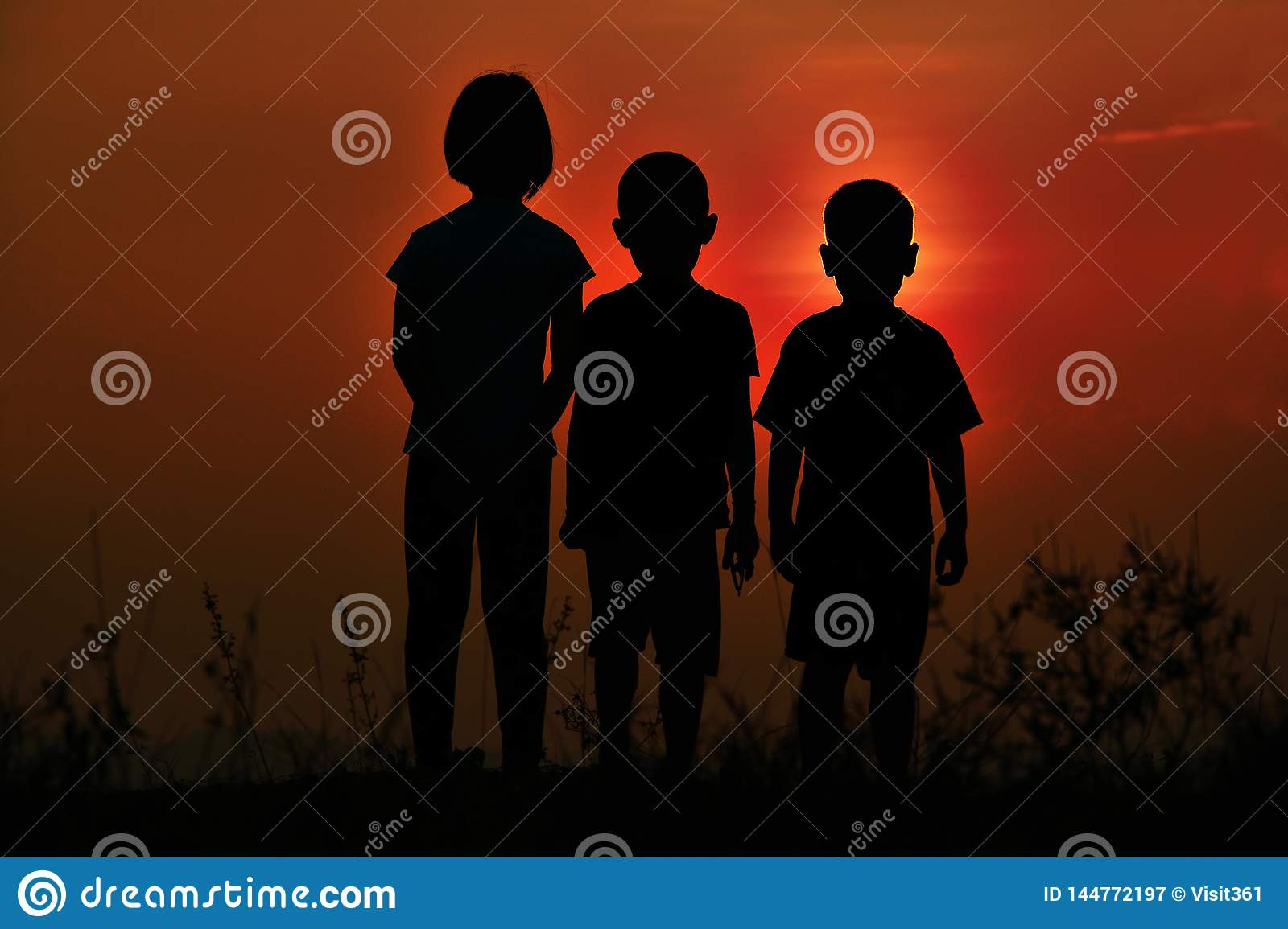 Black silhouette of three children standing together. There is a sky at sunset