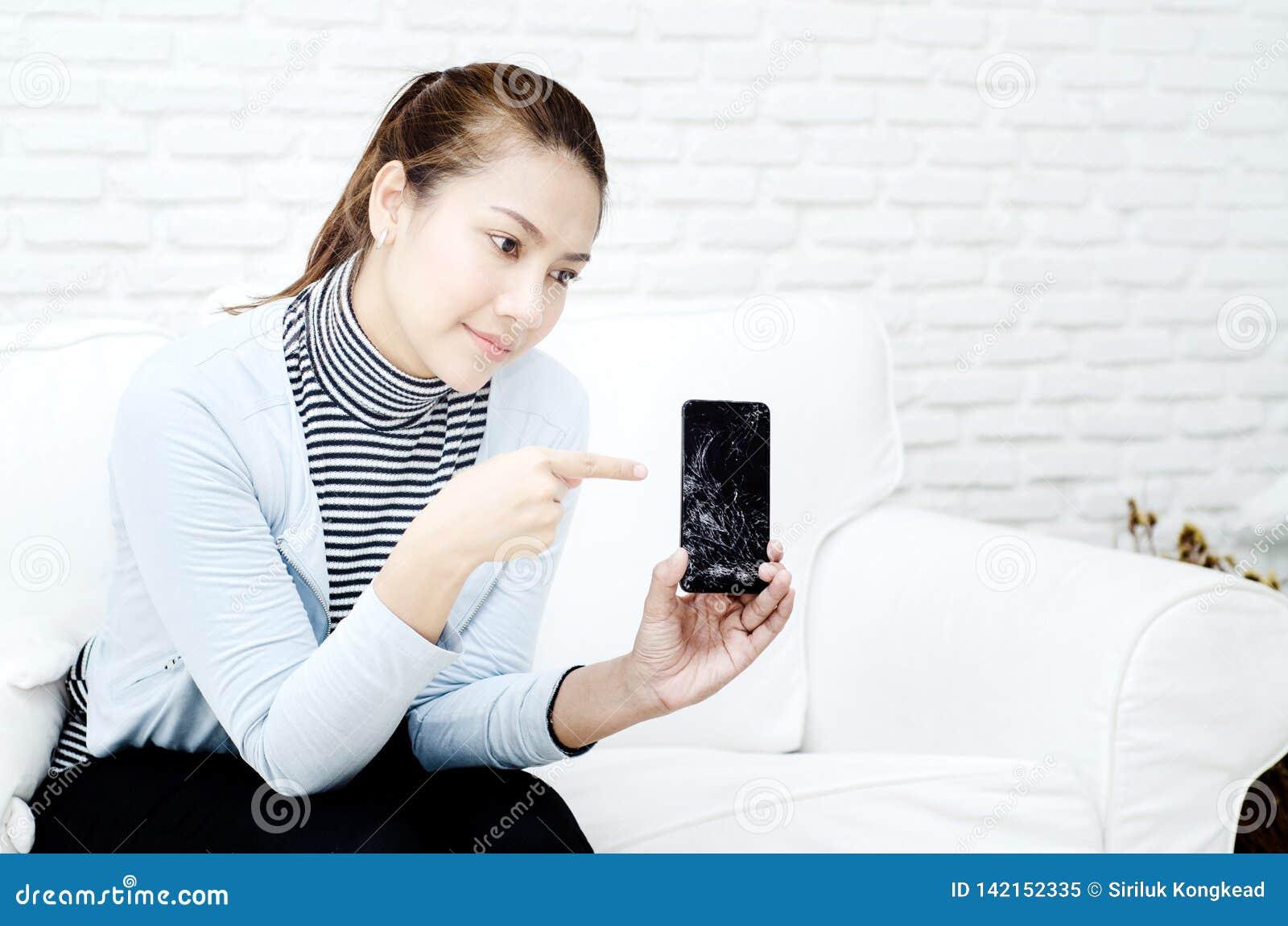 The broken mobile phone is in the hands of women.