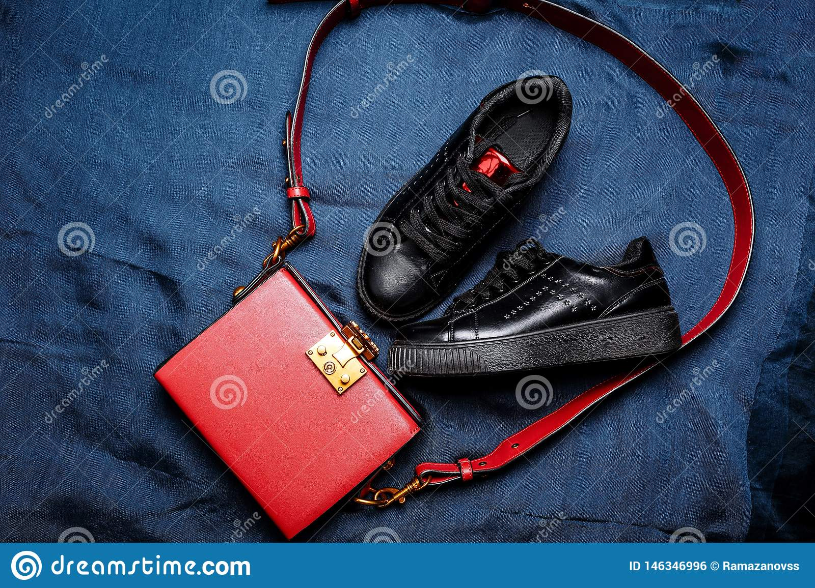 Black sneakers with red tongues and a red bag with a golden lock on a blue woven background
