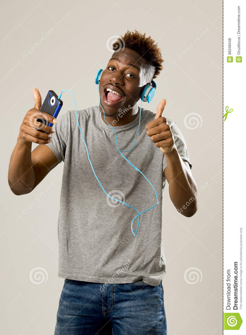 black student man with headphones and mobile phone listening to