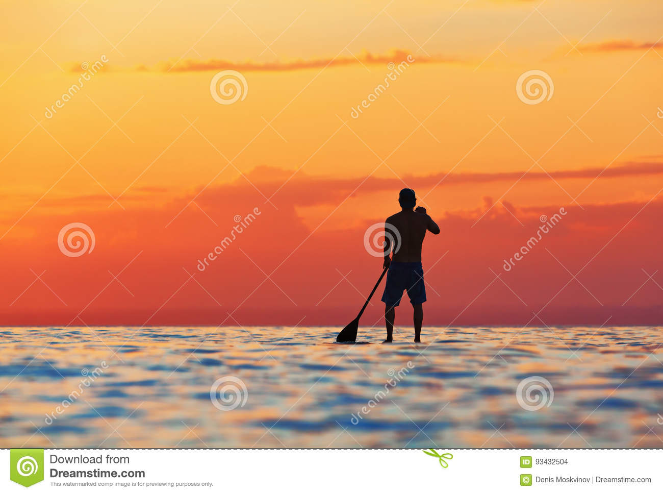 Black sunset silhouette of paddle boarder standing on SUP