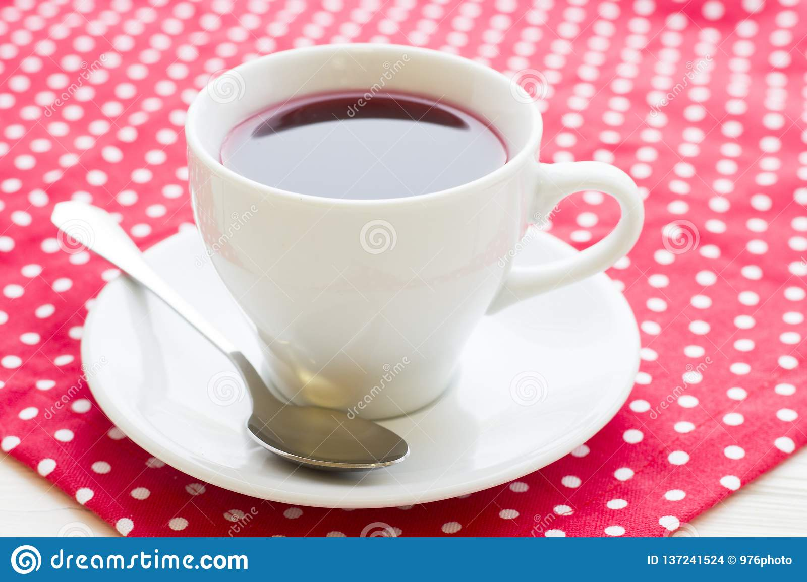 Black tea ceremony - a cup of tea, teapot, flowers on a red with white dots background