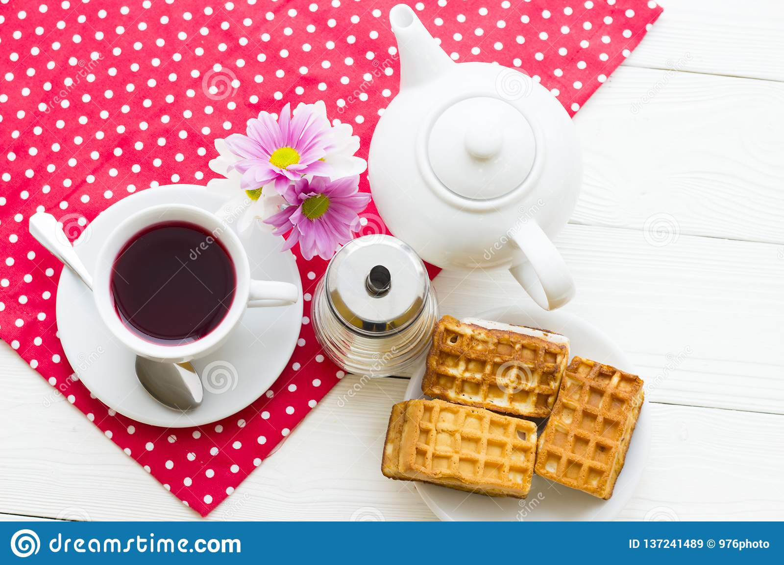 Black tea ceremony - a cup of tea, teapot, sugar, cakes, flowers on a red with white dots background