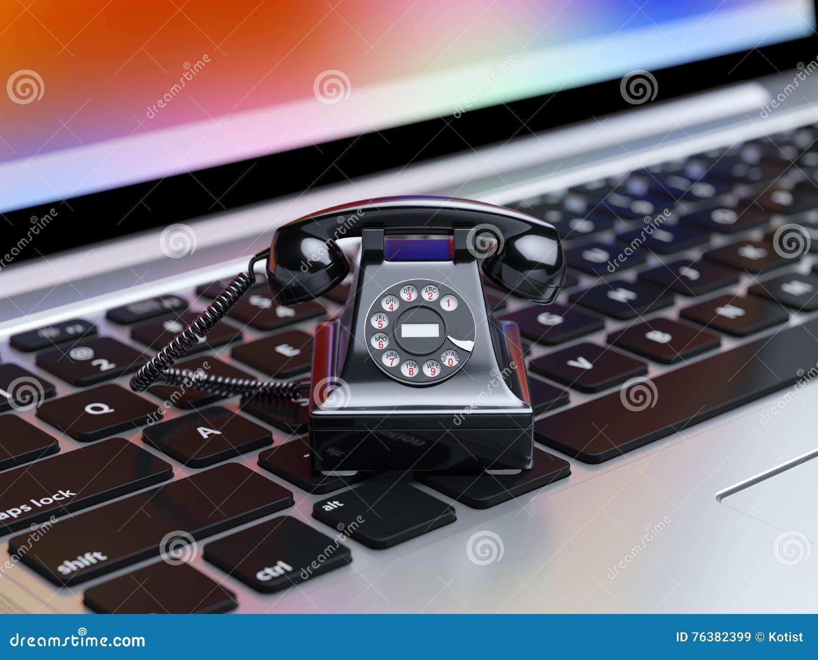 Black telephone on computer keyboard