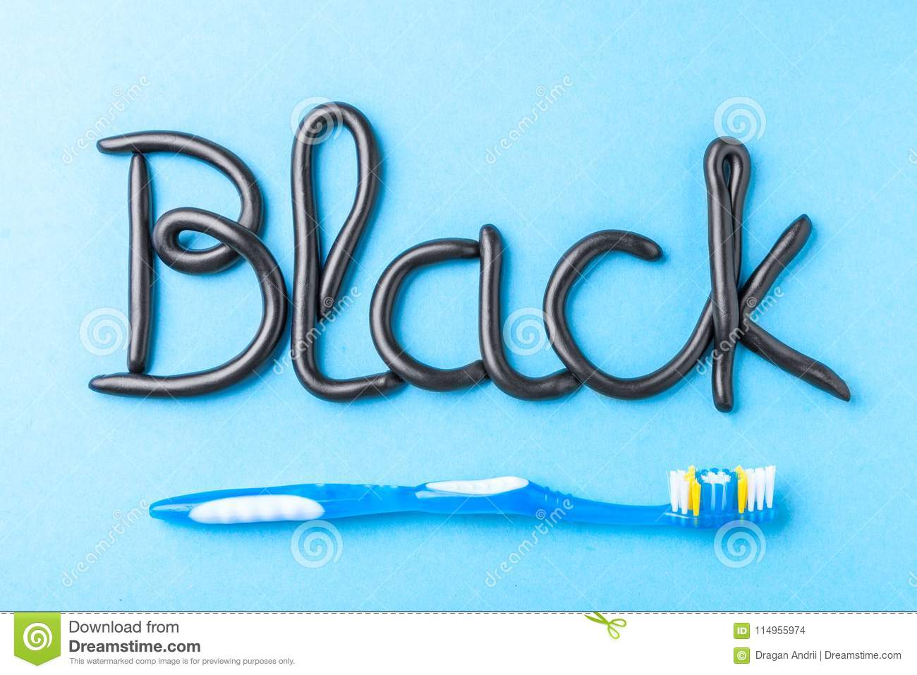 Black toothpaste from charcoal for white teeth. Word BLACK from toothpaste and toothbrush on blue
