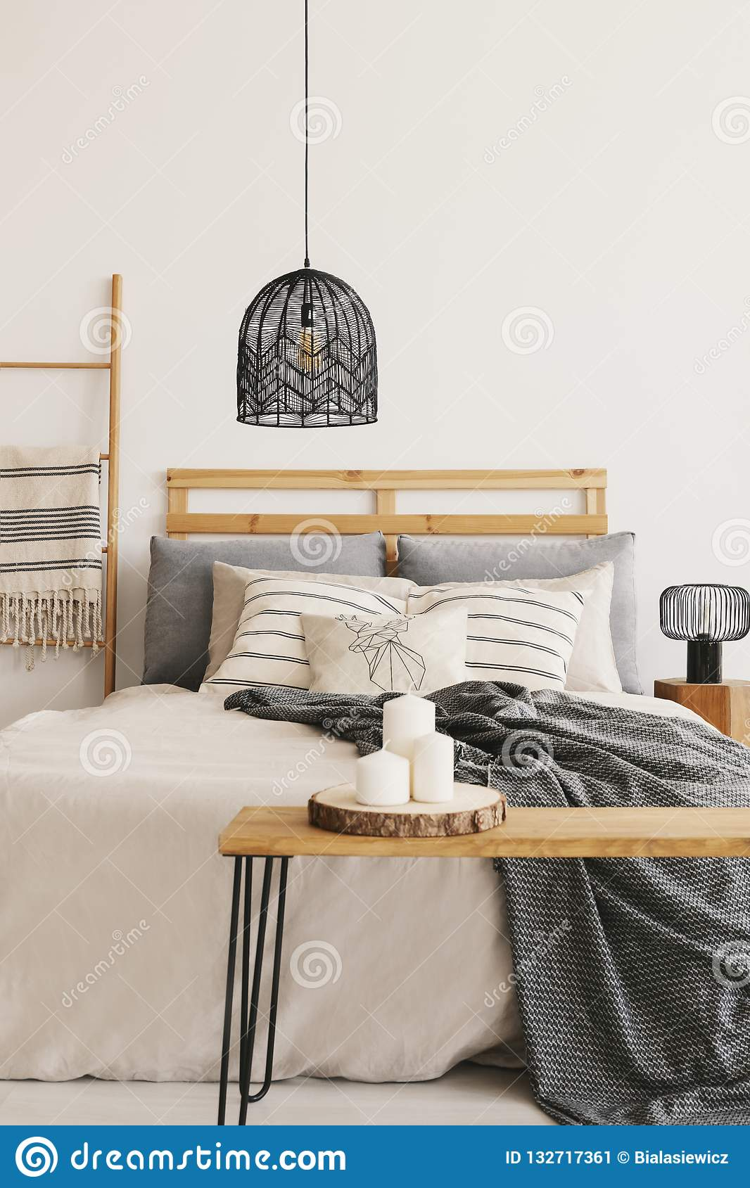 Black chandelier above king size bed with beige duvet, grey blanket and pillows, real photo with copy space on the empty