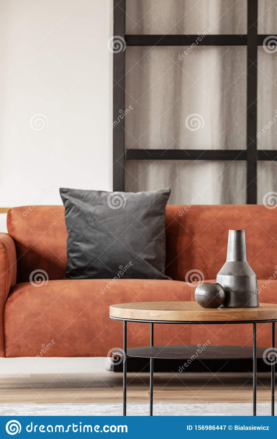 Black Vase On Wooden Coffee Table In Chic Living Room