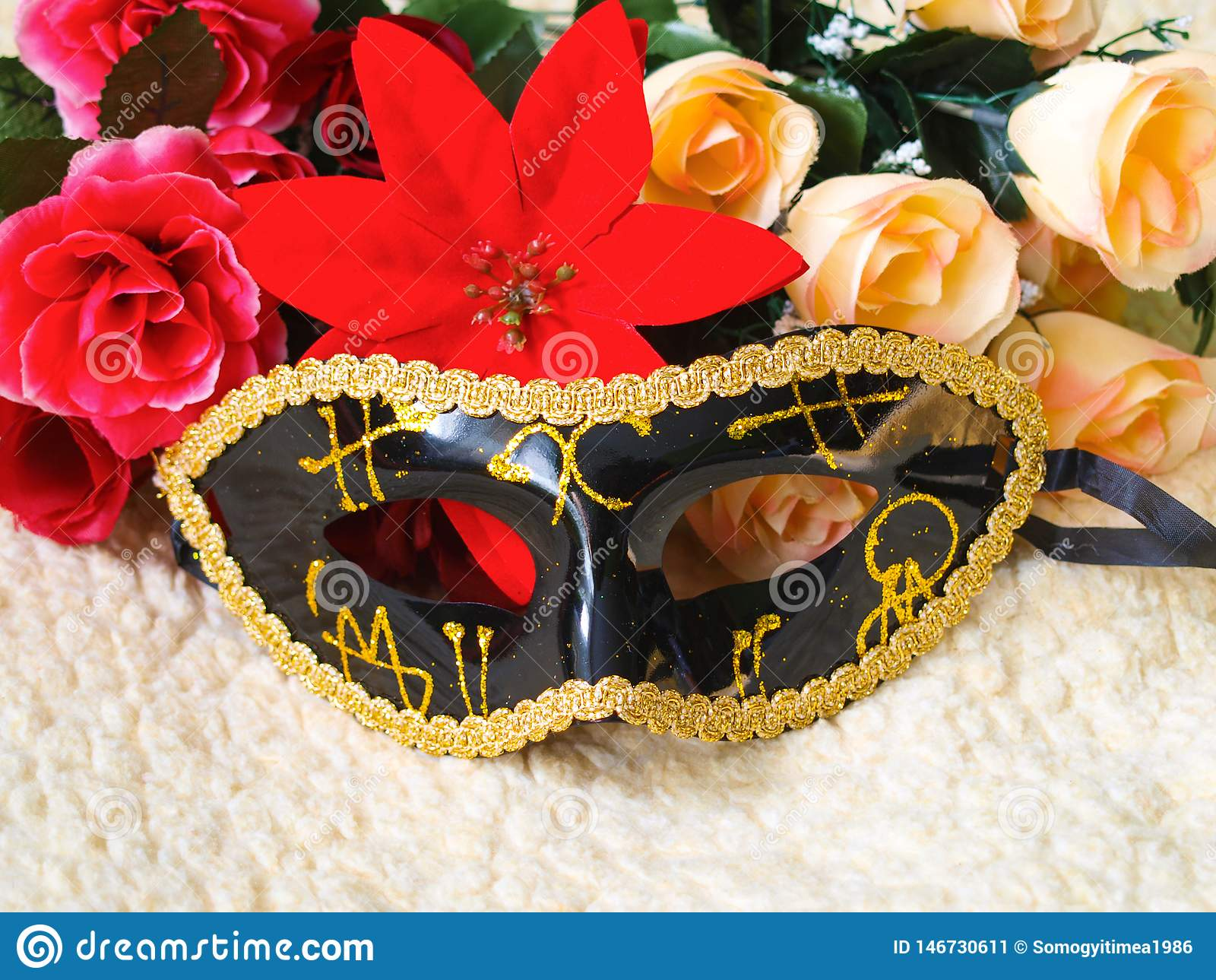 Black venetian mask with gold decorations, flowers