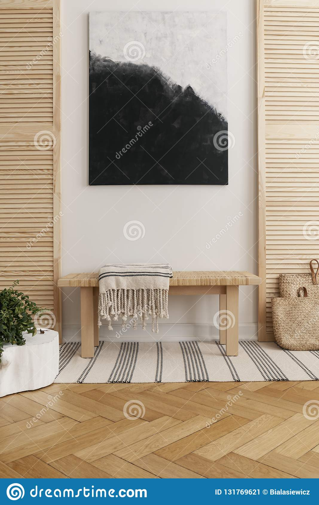 Black and white abstract painting above wooden table in natural designed interior