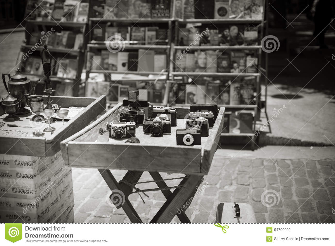 Black and white of antique used cameras on display at an outdoor