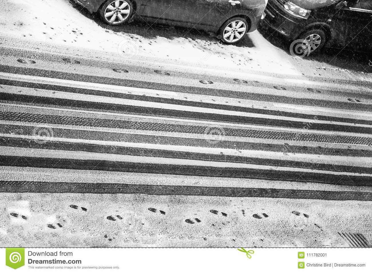 Black and white car treads and footprints in snow