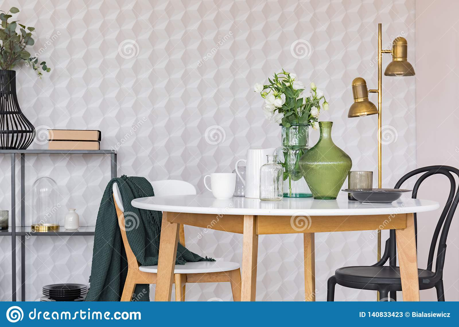 Black and white chair at wooden table in dining room interior with flowers and gold lamp. Real photo