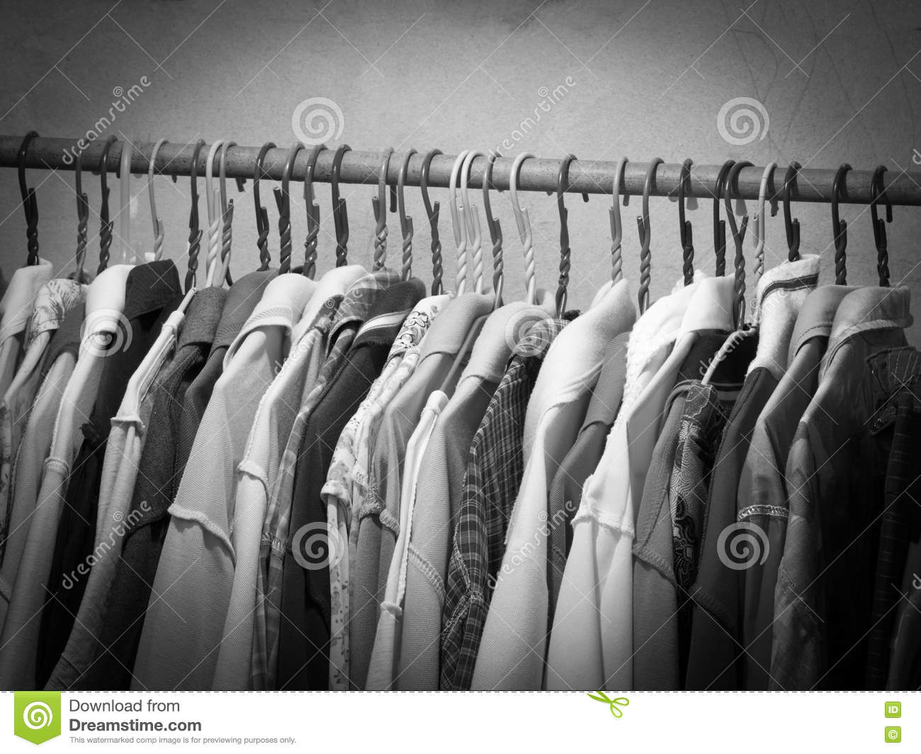 Black and white image of clothes hanging on hanger rack choice of