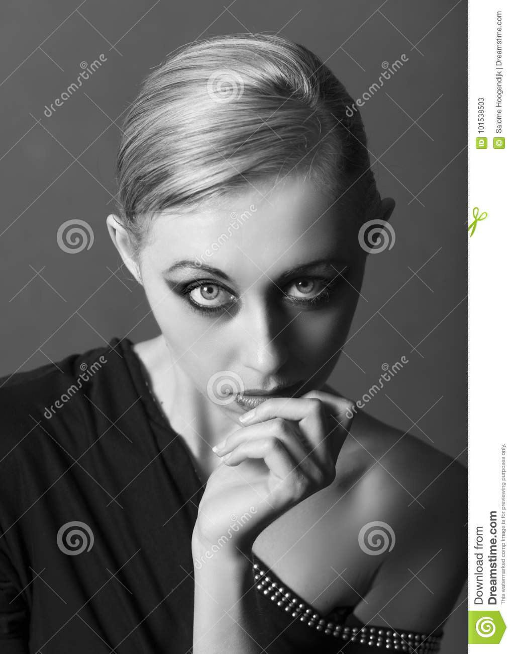 Black and white monochrome portrait of beautiful blonde woman wearing an off the shoulder black top and dramatic, edgy makeup, posing with her hand to her ...