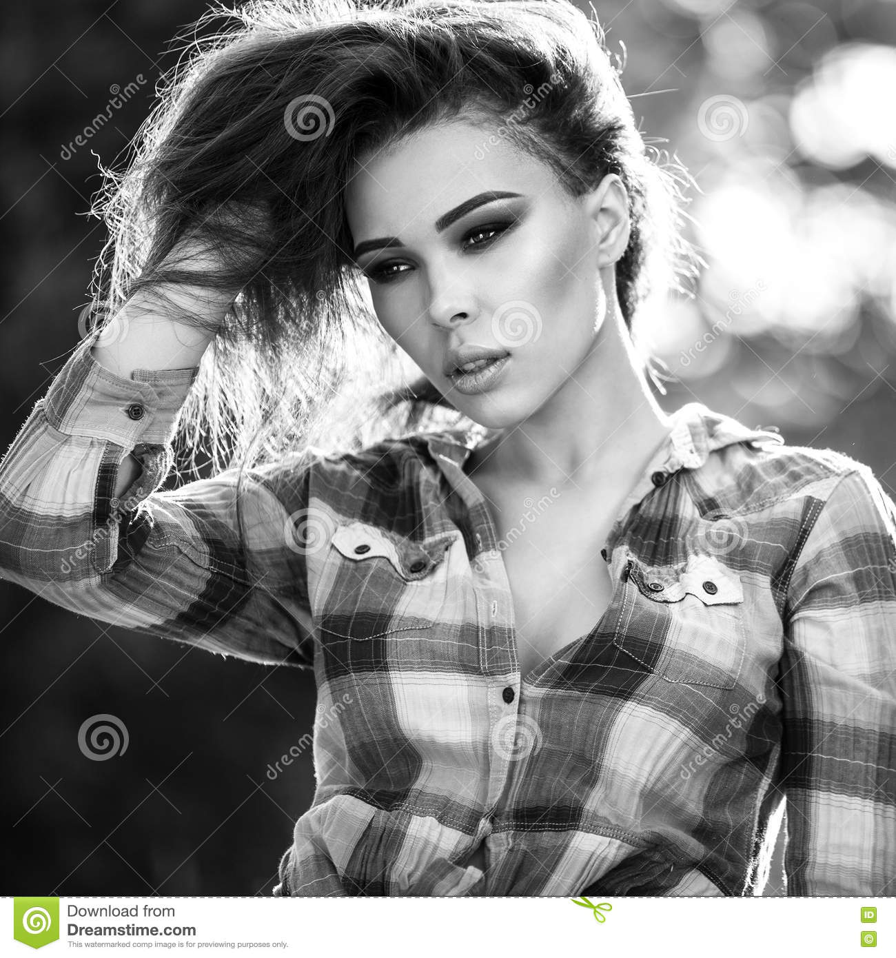 Black white outdoor portrait of beautiful woman agains nature background