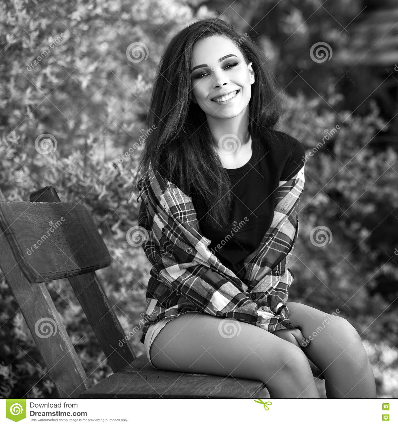 Black white outdoor portrait of siting beautiful young brunette