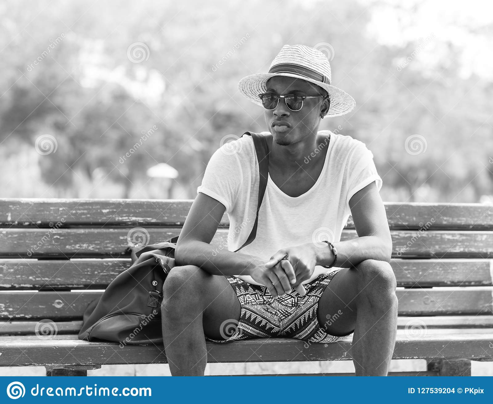 Black and white photo of an african american man watching things from a park bench wearing young millenial cultural clothing