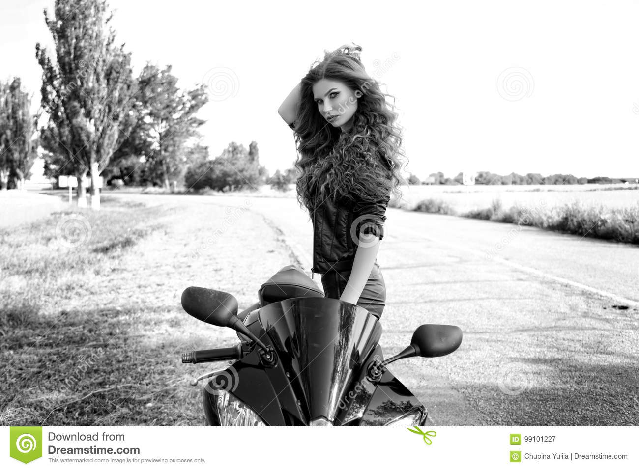 Black and white photo of a beautiful biker girl with a motorcycle