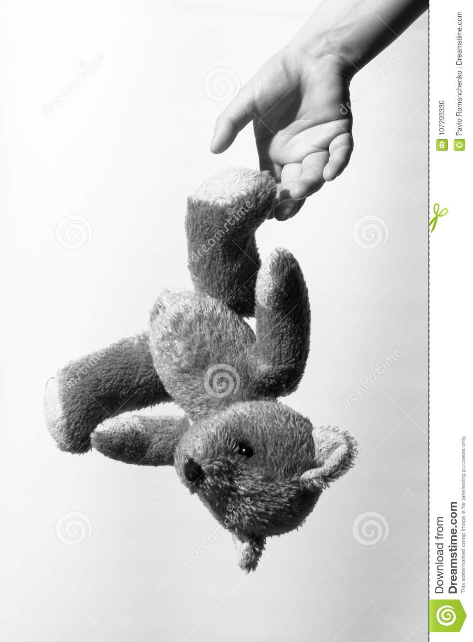 Black and white photo of a girl`s hand throwing a teddy bear