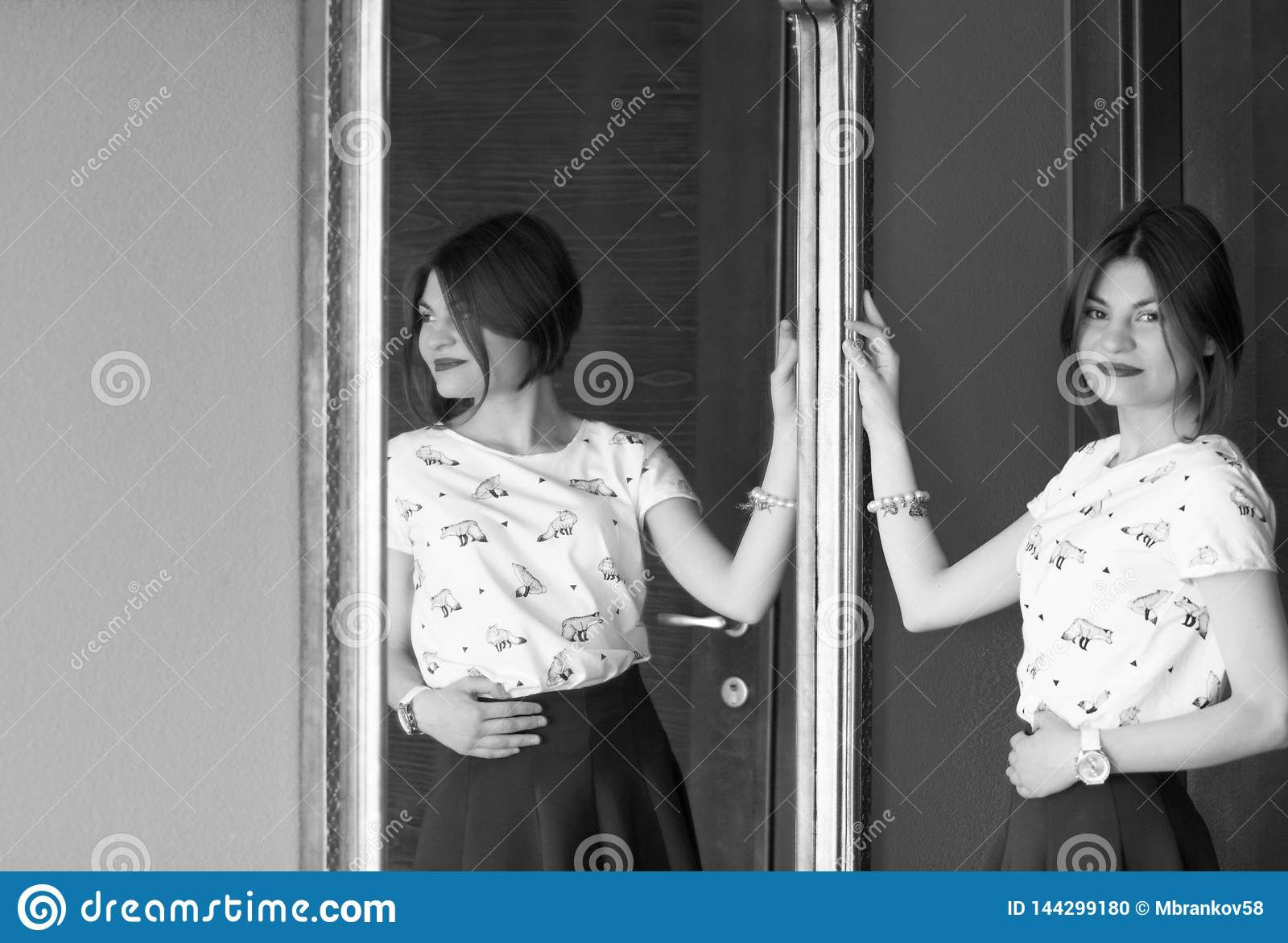 Black and white photo. The girl is seen from the side in the mirror.