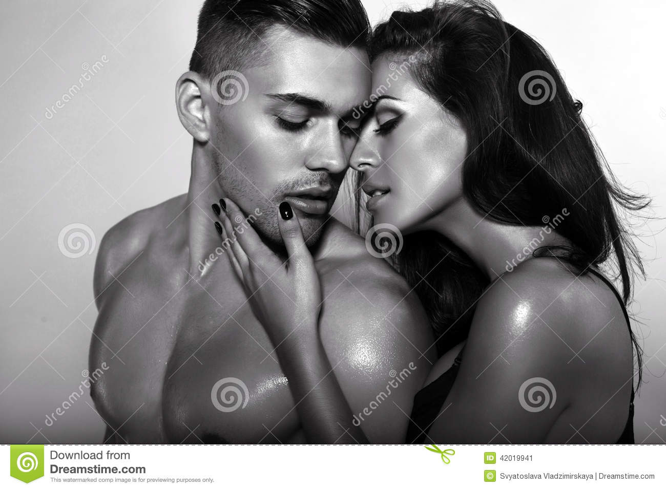 Black and white fashion portrait of naked couple posing at studio