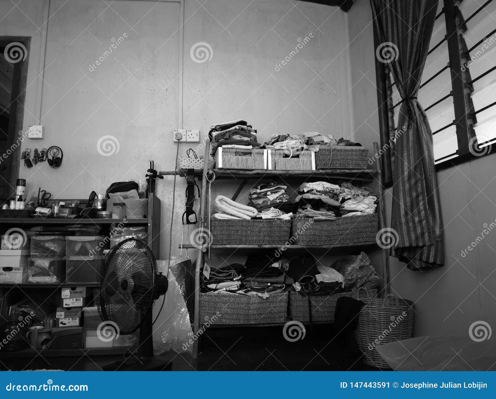 A black and white photo of a tiny homemade small closet.